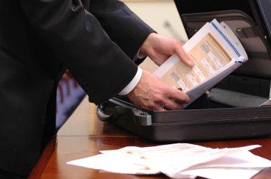 Businessman holding overloaded briefcase
