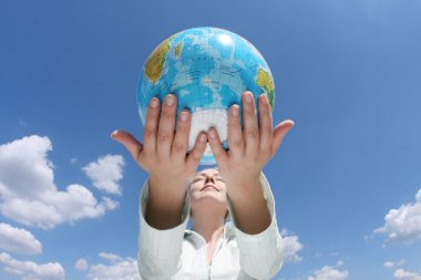 Woman holding a globe under blue sky