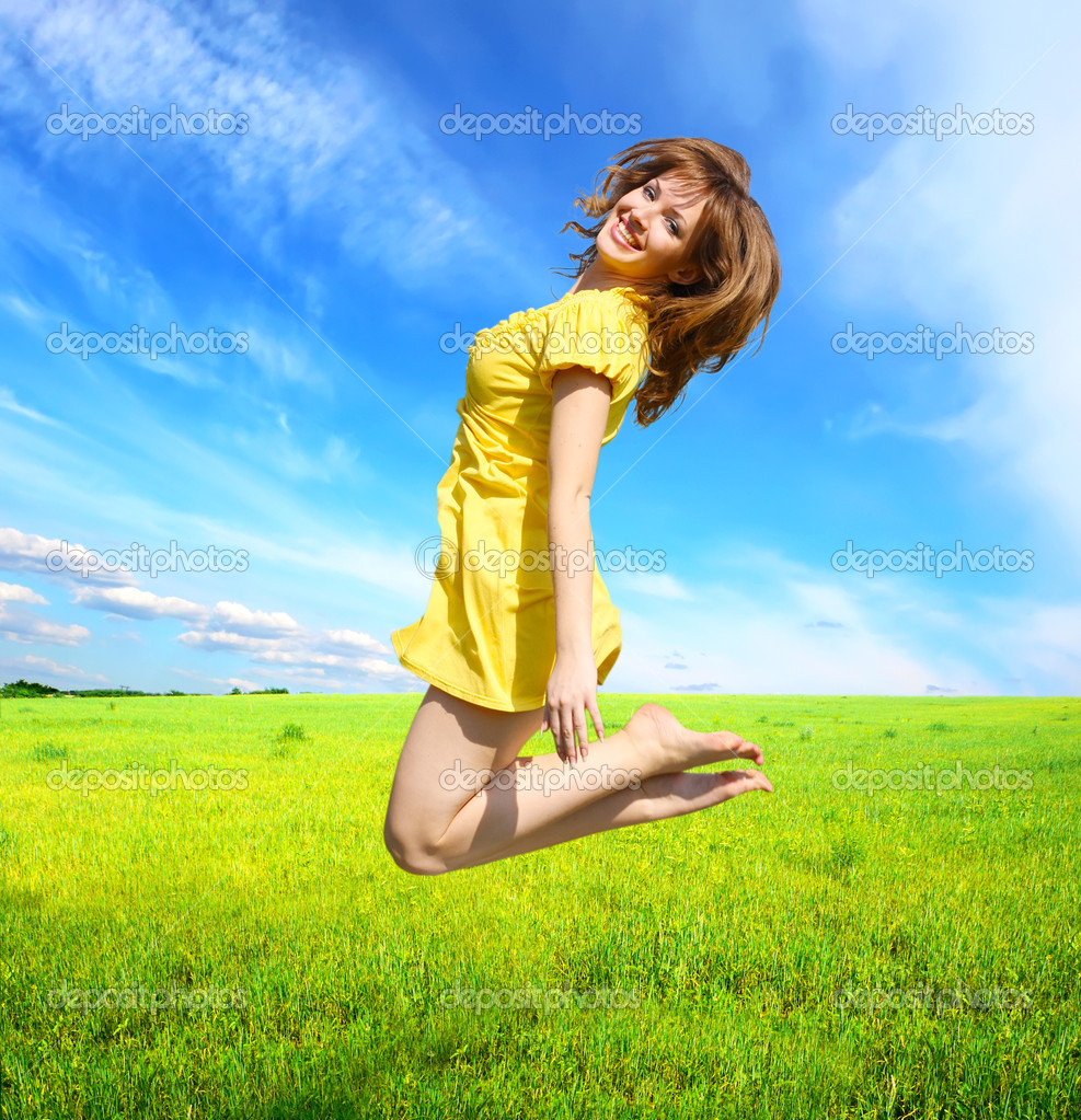 Happy young woman jumping in meadow