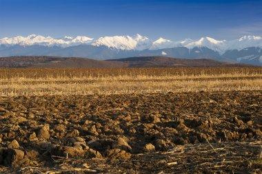 Mountain range snow peaks plowed field