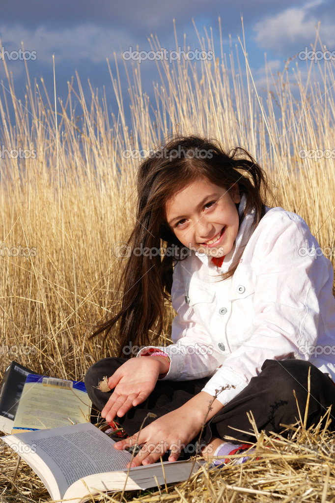 Little cute girl reads on the meadow