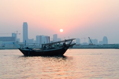 Bahrain city silhouette and fishing dhow