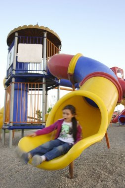 Little girl slides in a playground