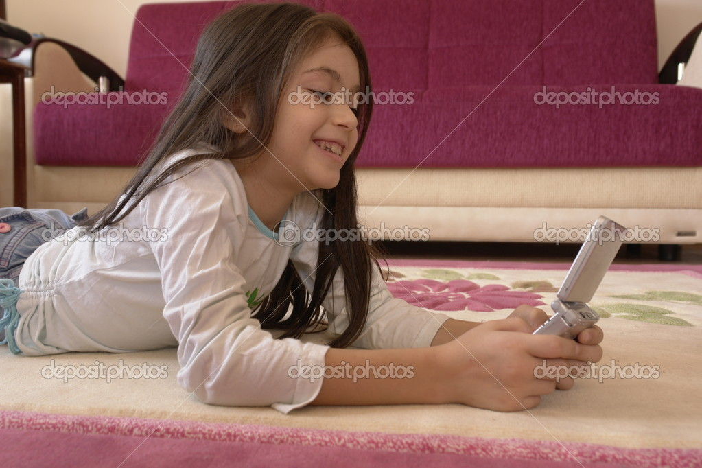 Little Girl Plays Gameboy With Passion Stock Photo