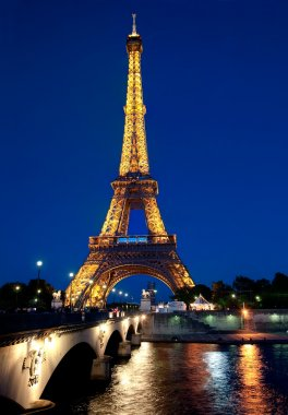 Eiffel tower illuminated at dusk.