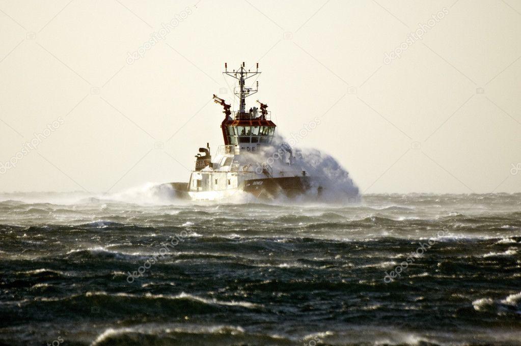 Tuboat ploughing a rough sea
