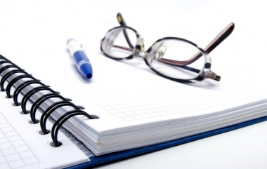 Notebook with pen and glasses