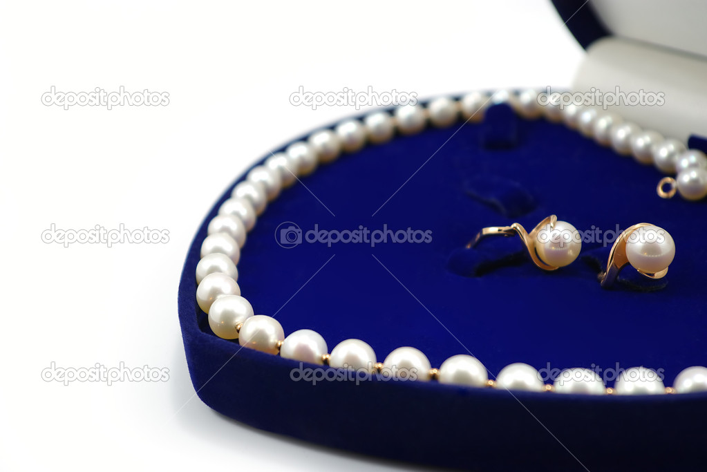 Pearl necklace and two earrings in blue heart-shaped box on white background