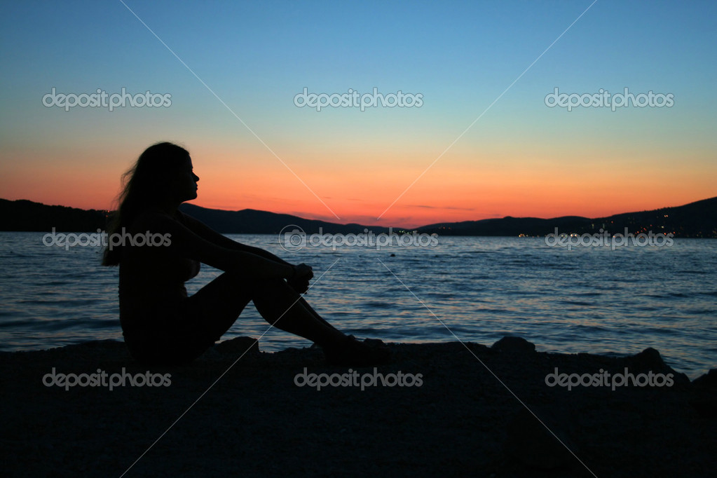 Beautifull woman sitting on the beach
