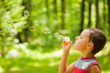 Cute kid blowing soap bubbles