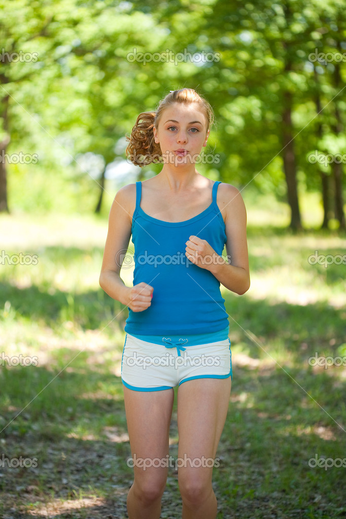 Sporty blonde girl doing fitness outdoor