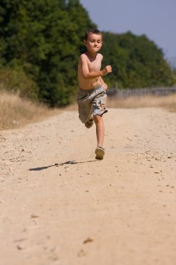 Boy running on dusty road