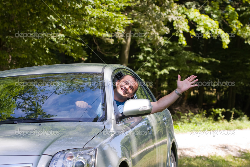 Man waving hand from car