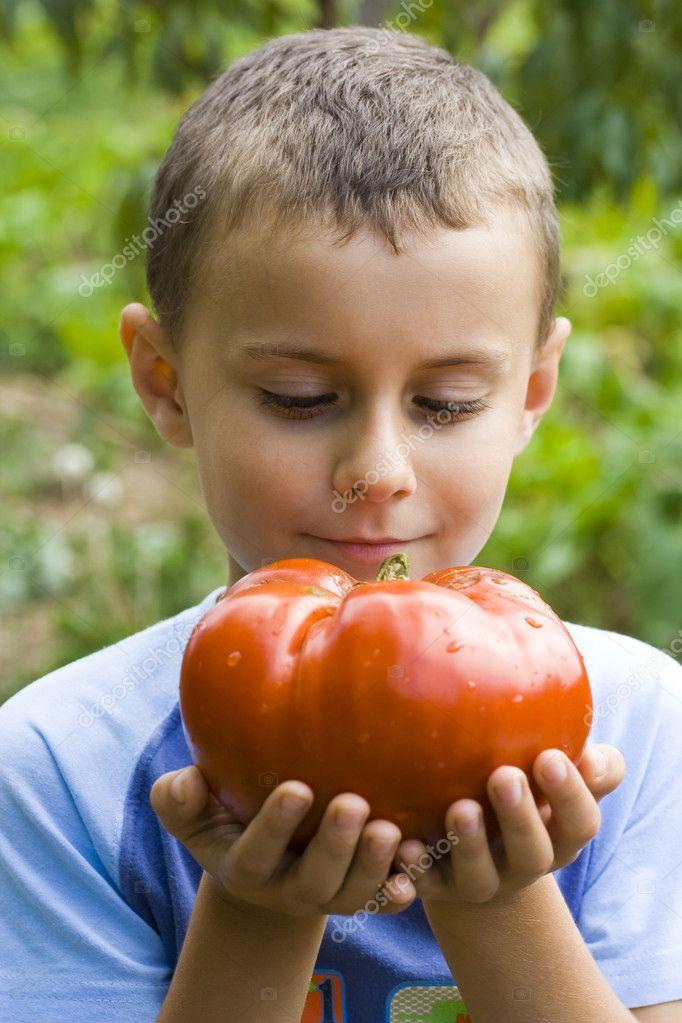 Boy with giant tomato