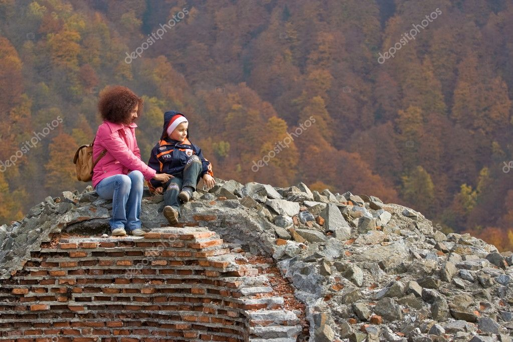 Mother and son climb on castle ruins