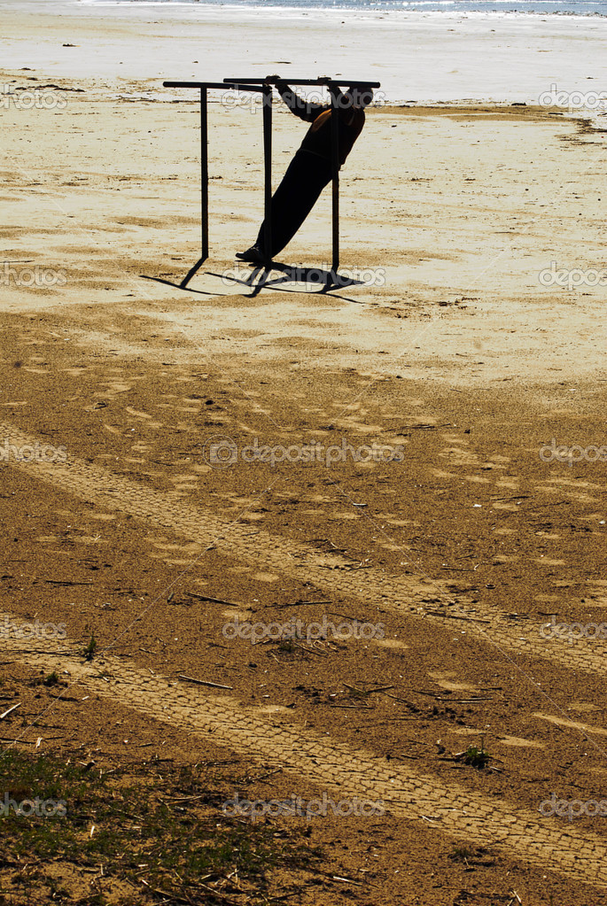 Man doing parallel bars on the beach