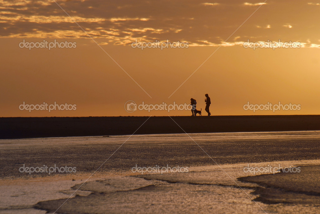 Couple walking on the beach at sunrise