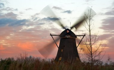 Windmills at windy sunset