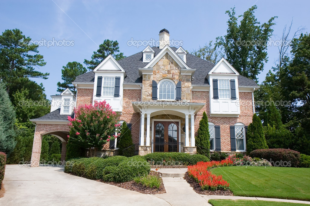 brick and stone house with flowers stock editorial photo