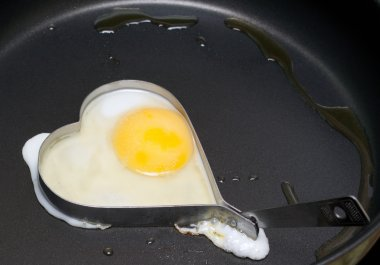 Fried egg in iron form heart crop