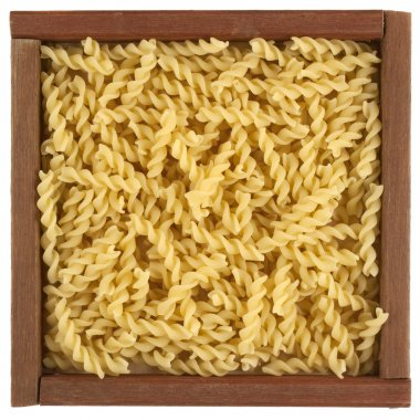 Uncooked fusilli pasta in wooden box
