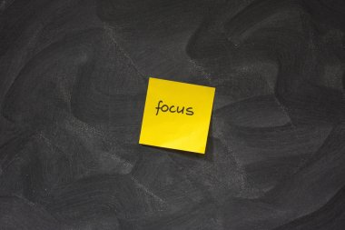 Focus on yellow sticky note against blackboard