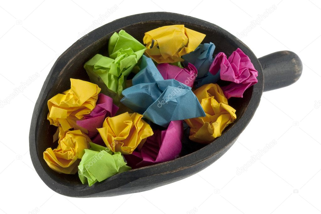 Recycling concept - colorful crumbled paper (sticky notes) on a rustic, wooden scoop, isolated on white