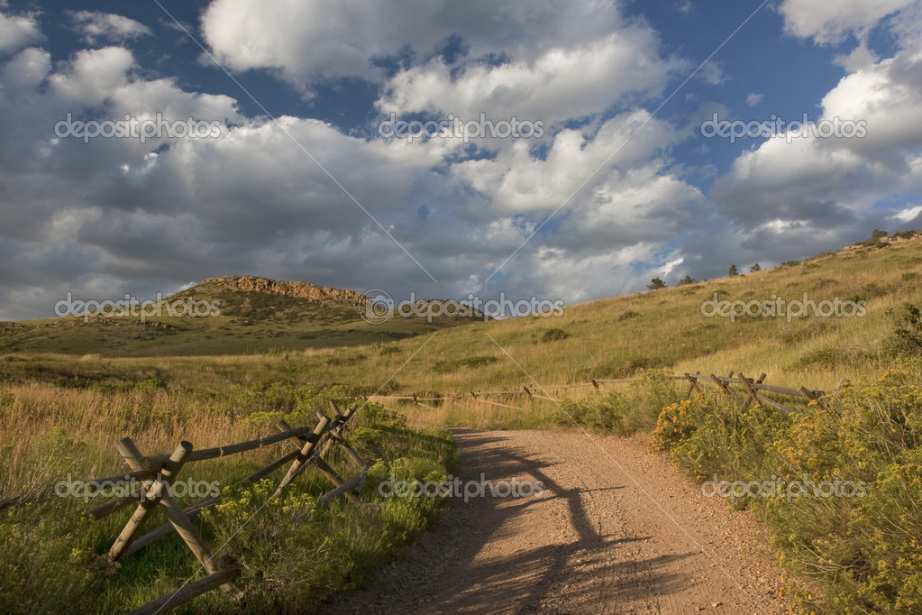 Dirt road and wooden fence at foothills of Rocky Mountains near Fort Collins, Colorado, late summer