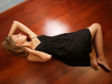 Young blond woman on wood floor