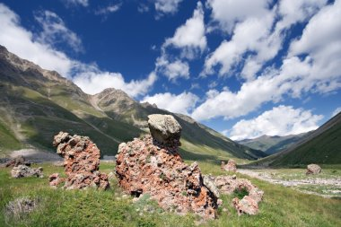 Rocks in mountain grass valley, Caucasus