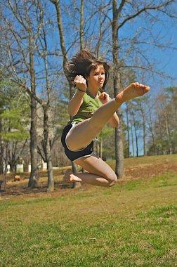 Teen girl performing martial arts kick