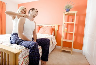 Woman Massaging Man's Shoulders in Bedroom