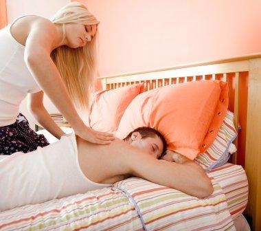 Woman Massaging Man on Bed