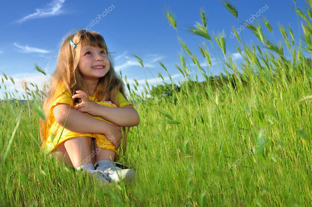 Dreaming girl in a fresh green grass