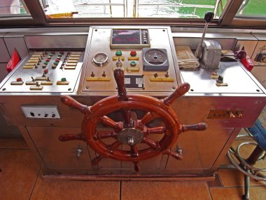 A wooden steering wheel on a sailboat