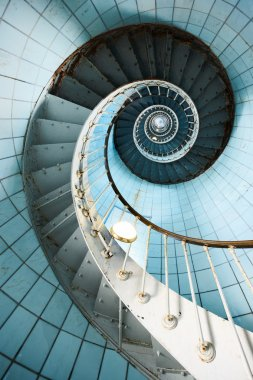 A spiral staircase going up with blue tiled wall