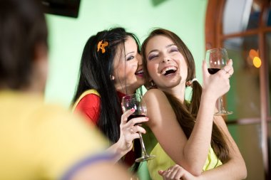 Boy with two girls are drinking wine