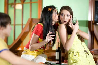 Girls with boy are drinking wine