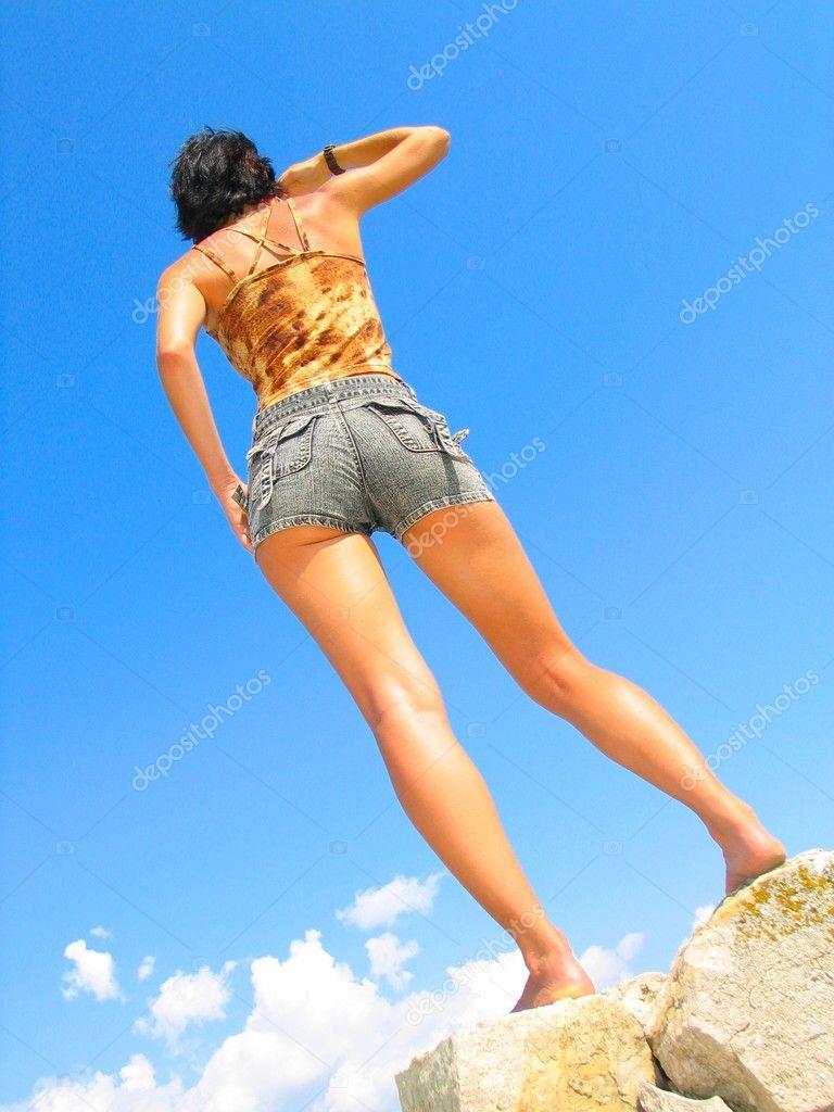 Slender girl against blue sky