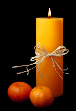 Lit candle with ribbon and clementines