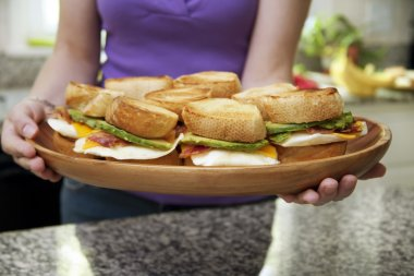 Woman Holding Platter of Egg Sandwiches