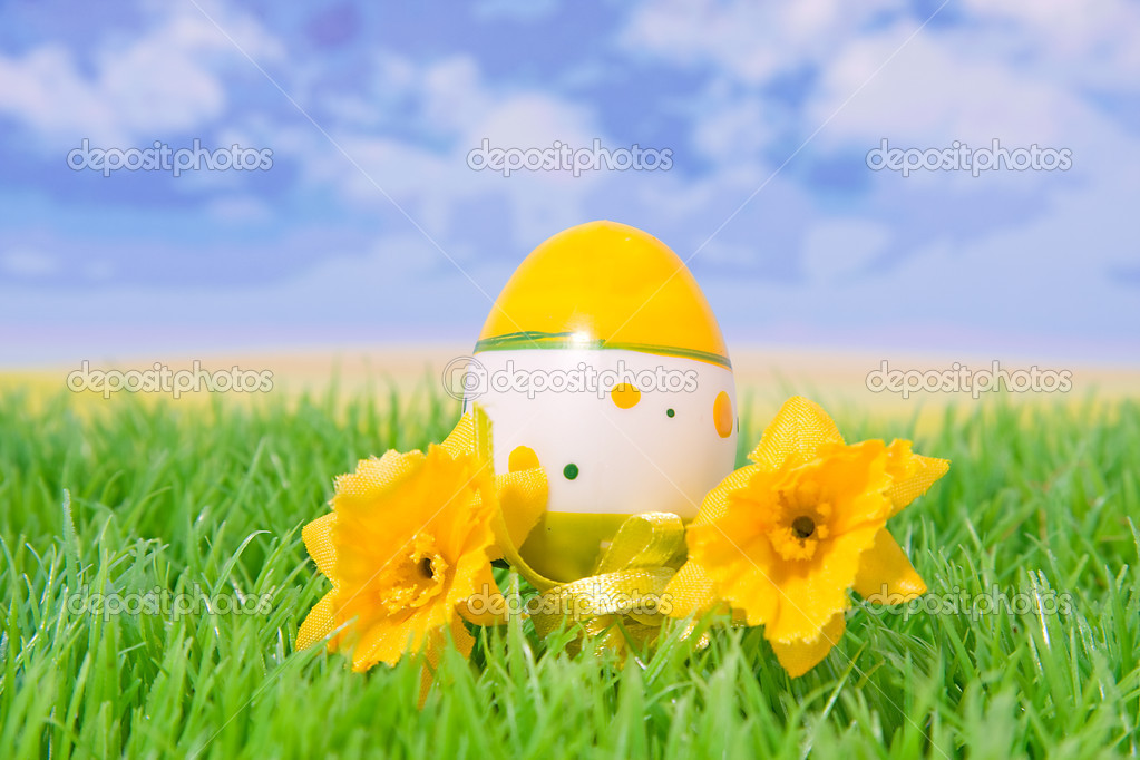Plastic Easter Egg On Grass With Flowers Stock Photo