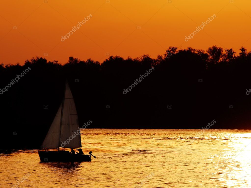 Sail boat on river at sunset