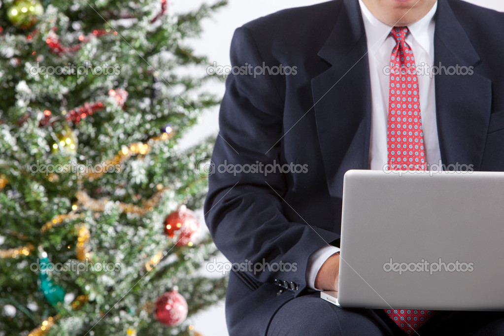 Businessman with pc by christmas tree