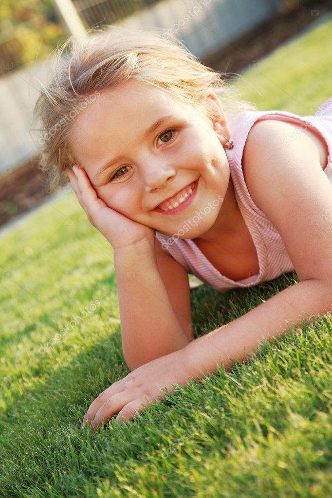 Happy cute girl relaxing on a grass field