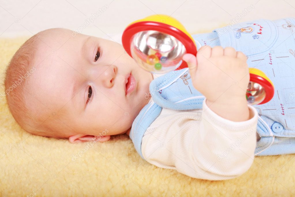 Portrait of cute newborn playing with rattle