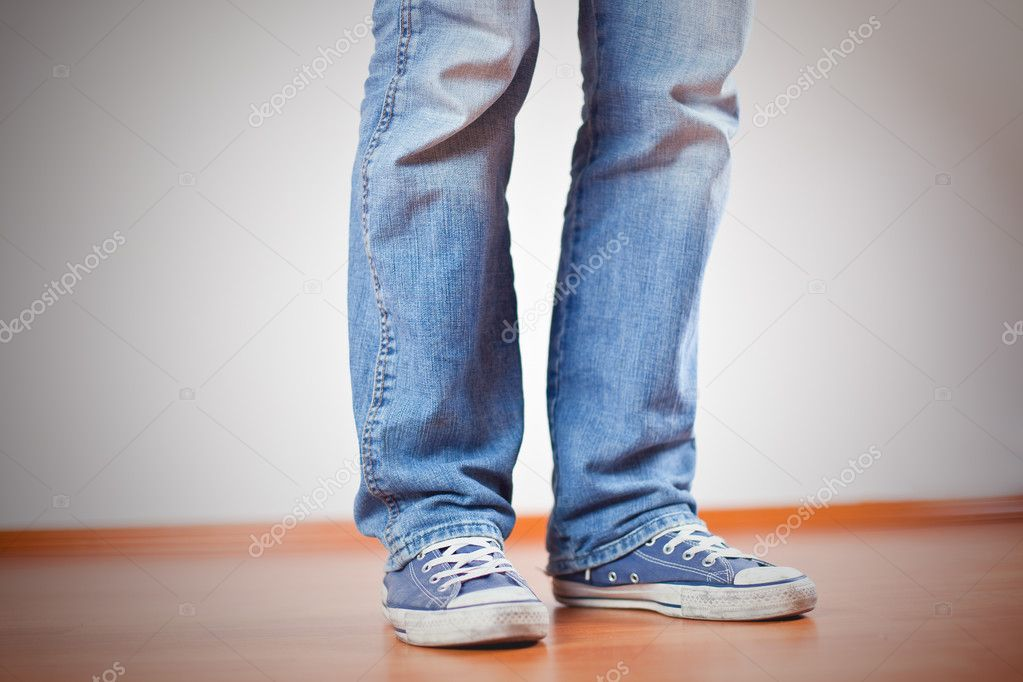 9c0e8c24148 Ανθρώπινο πόδι με τζιν και αθλητικά παπούτσια στο ξύλινο πάτωμα — Εικόνα  από ...