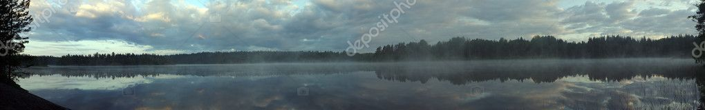 Morning fog on wild forest lake