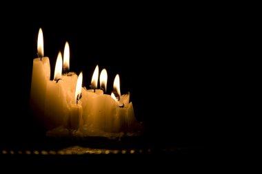 White candles burning in dark