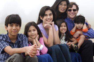 Mutiracial family sitting on beach